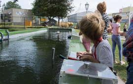 Kinderen met bestuurbaar bootje in BPT museum achtergrond-k